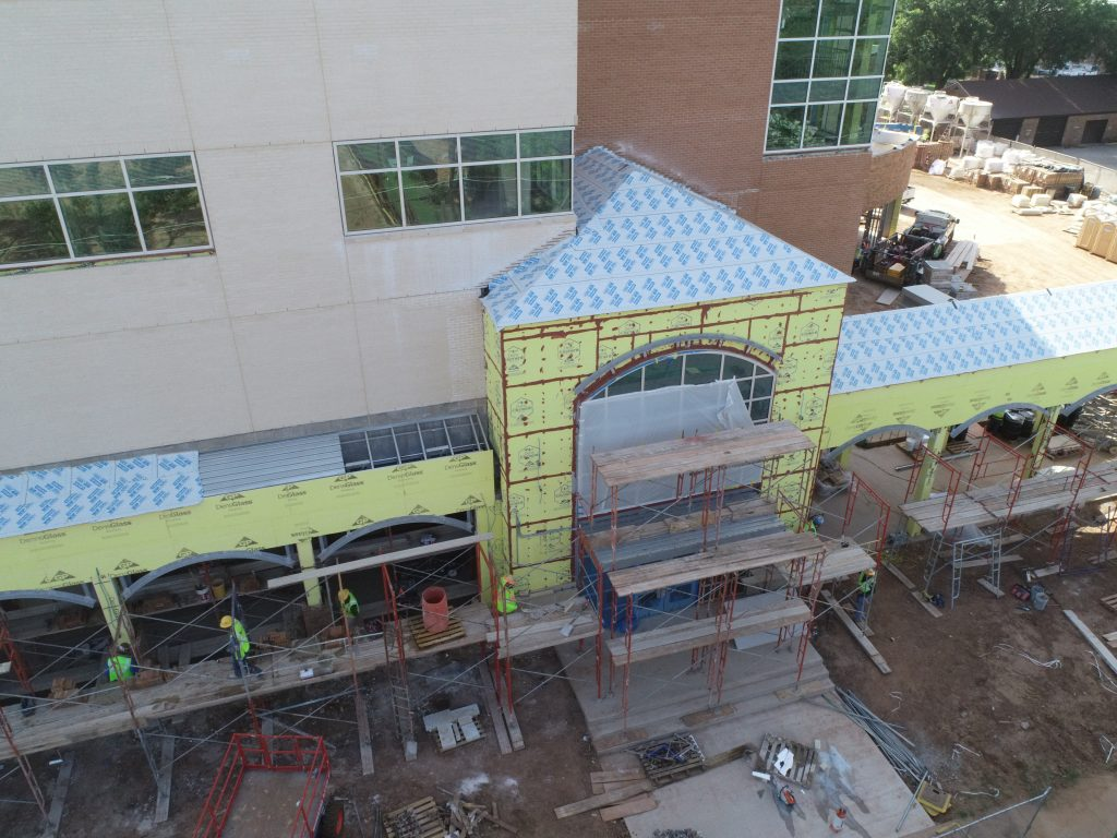 Crews work on the exterior of the building to prepare for students in late August.