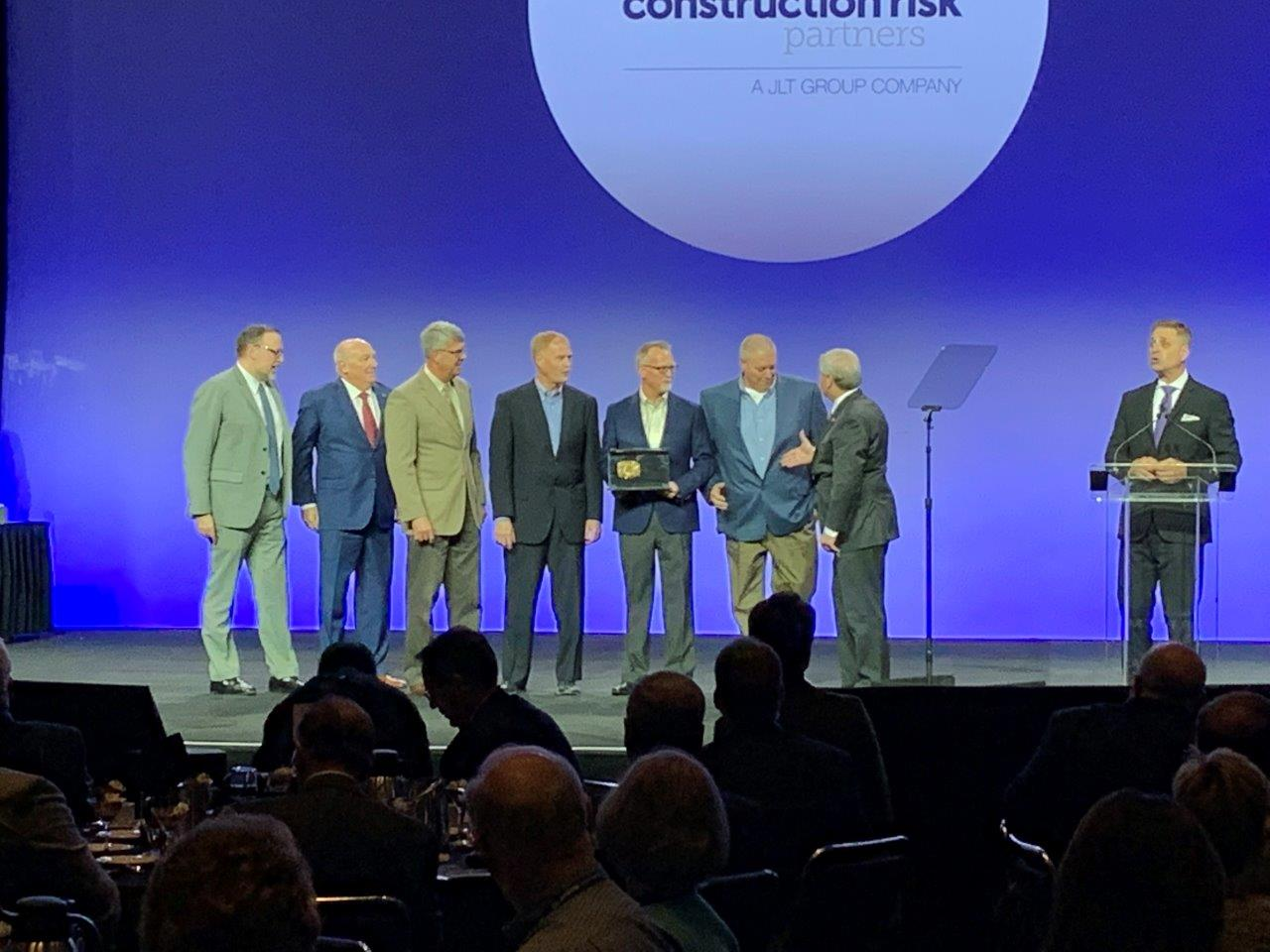 APS Senior Project Manager Dewayne Keegel (third from left) joins Sundt employee-owners Ken Dean, Steve Roberts and Derek Neill in accepting the 2019 JLT Build America Award.