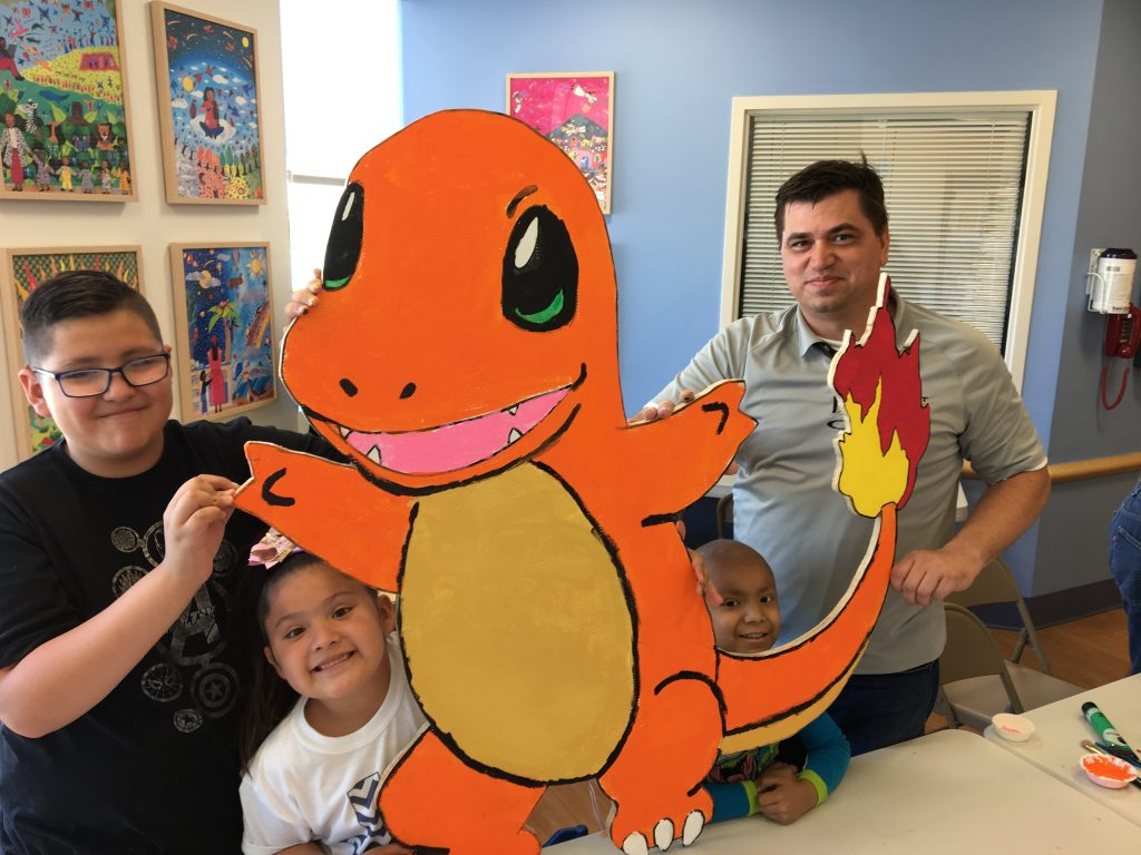 Sundt Project Manager Larry Kurtz and El Paso Children's Hospital oncology patients display their freshly painted Charmander