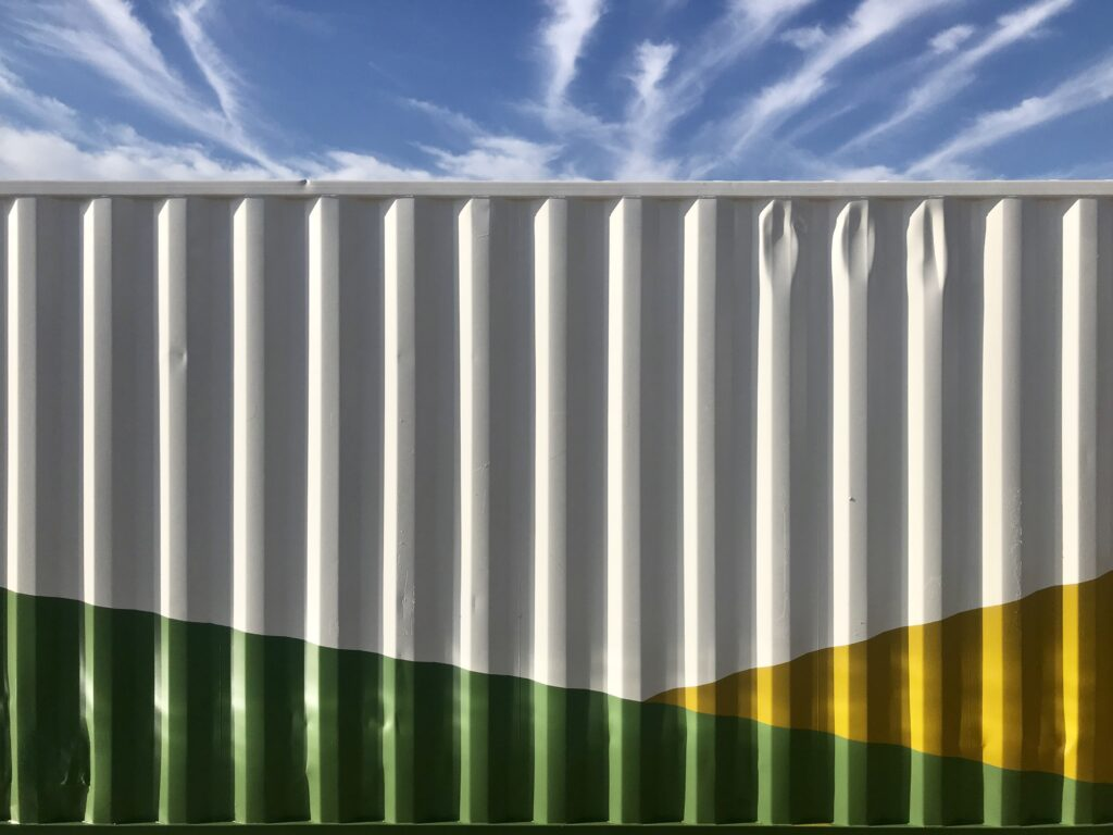 close up of exterior of shipping container painted green and yellow for sustainability
