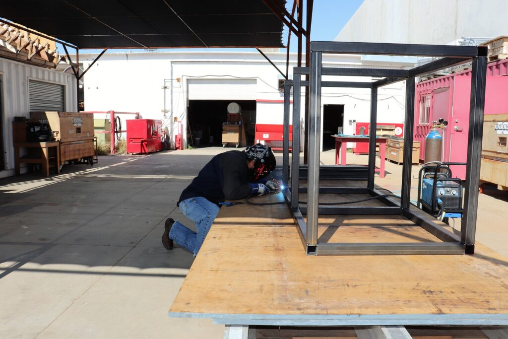 Craft Training Instructor Josue Ponce welds 2 inch square tube into a bed/desk combo