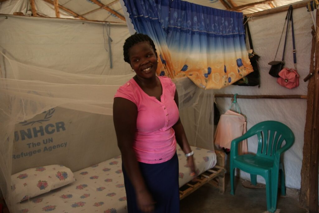 Woman who is healthcare worker stands in tent living quarters at Palorinya refugee Camp
