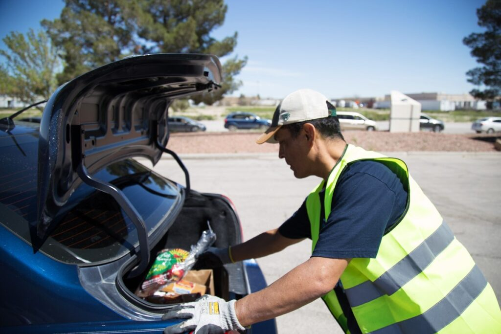 A volunteer loads food into the trunk of a family's car at El Pasoans Fighting Hunger in El Paso, Texas