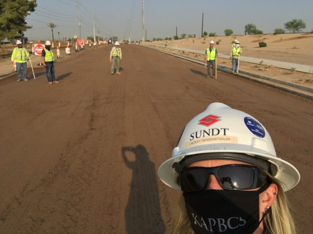 selfie of construction project manager and her team standing on a road bed in Arizona